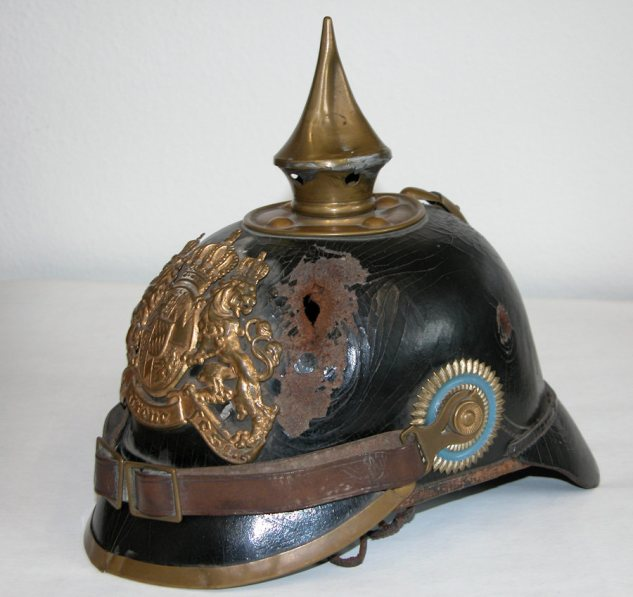 "Pickelhaube of a soldier of K.B.IR 16. The owner was wounded in 1914. A piece of shrapnel pierced Pickelhaube and skull and brain before exiting on the other side. The owner survived the terrible wound and died in 1977. (Exhibit in "" Haus der Bayerischen Geschichte"" - Regensburg"